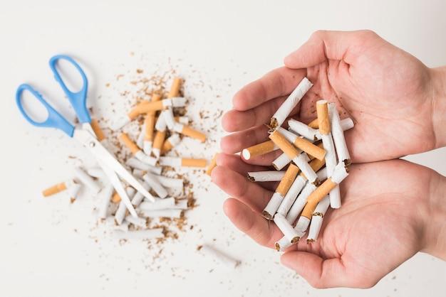 Mãos, de, um, pessoa, segurando, cigarros quebrados, sobre, scissor, e, cigarros quebrados