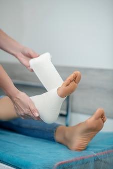 Mãos de um profissional de saúde enfaixando profissionalmente o tornozelo com bandagem elástica, sem rostos