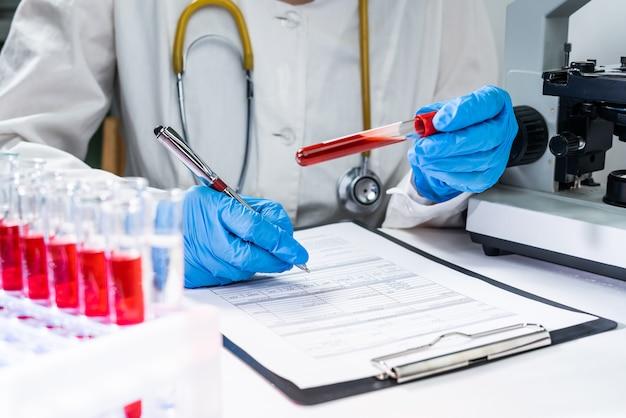 Mãos de um técnico de laboratório com um tubo de amostra de sangue e um suporte com outras amostras