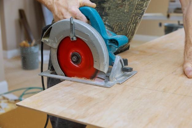 Mãos de um trabalhador corta madeira compensada com uma serra circular