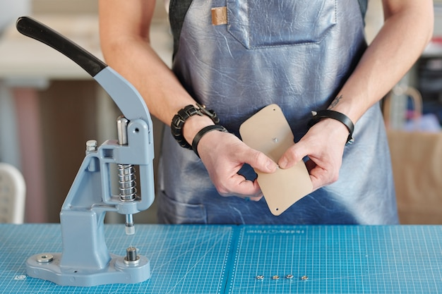 Mãos de um trabalhador em couro criativo em um avental de couro preto colocando minúsculos botões metálicos em uma amostra bege claro enquanto fica de pé ao lado da mesa