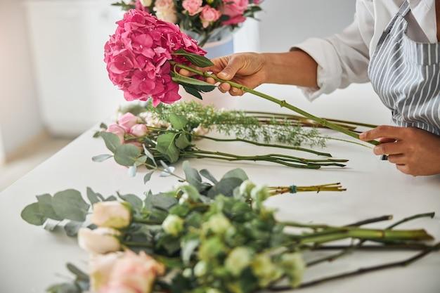 Mãos de um trabalhador florista profissional fazendo um buquê