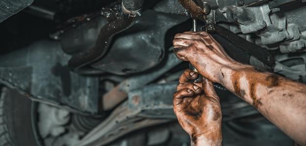 Mãos de um trabalhador no serviço de reparo do carro
