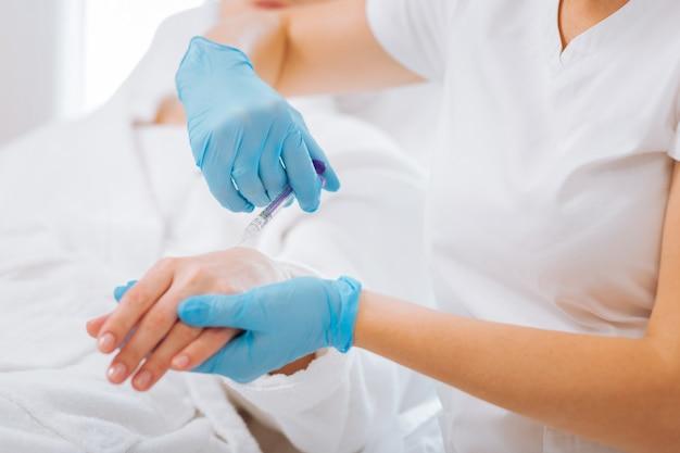 Mãos de uma bela mulher nas mãos de uma esteticista profissional durante a aplicação de uma injeção