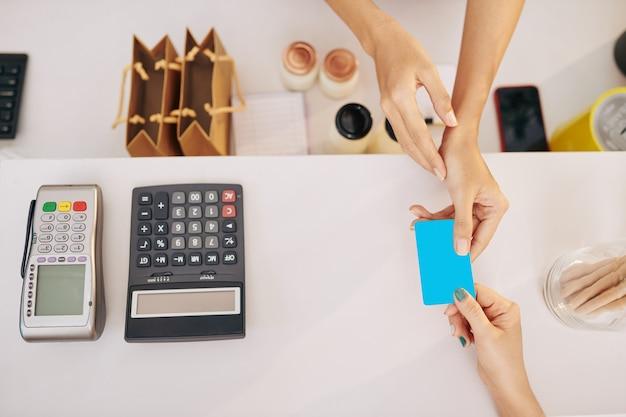 Mãos de uma cliente dando cartão de crédito ao barista para pagar o pedido, vista de cima