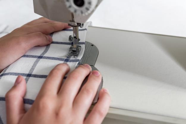 Mãos de uma costureira em uma máquina de costura no processo de costura com uma cópia do espaço
