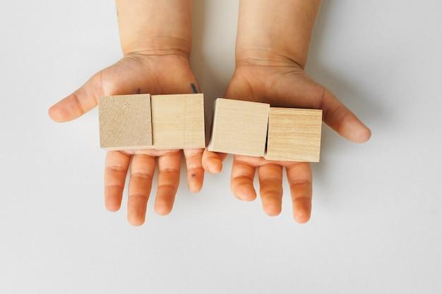 Mãos de uma criança com quatro blocos de madeira, vista de cima