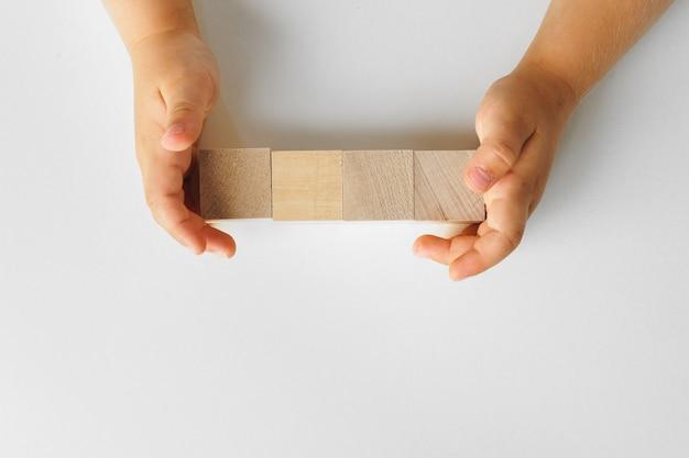 Mãos de uma criança com quatro blocos de madeira