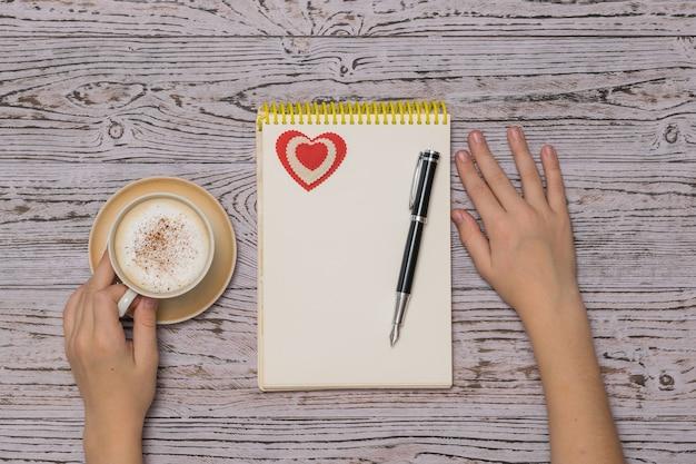 Mãos de uma criança com uma xícara de café, um caderno e uma caneta sobre uma mesa de madeira. café no processo criativo. postura plana.