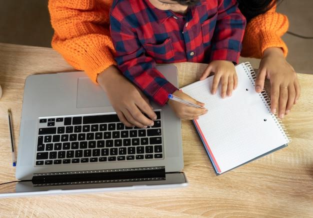 Mãos de uma criança e sua mãe escrevendo em um caderno sobre uma mesa em casa