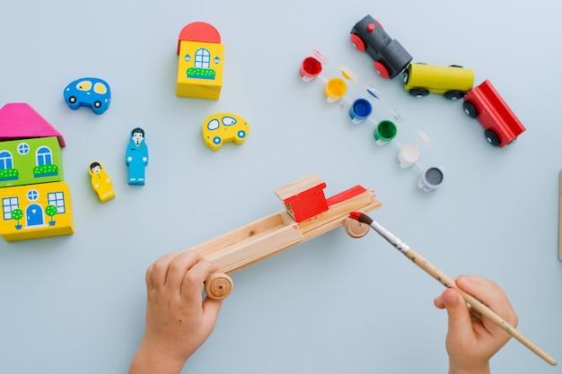 Mãos de uma criança pintar uma máquina de madeira