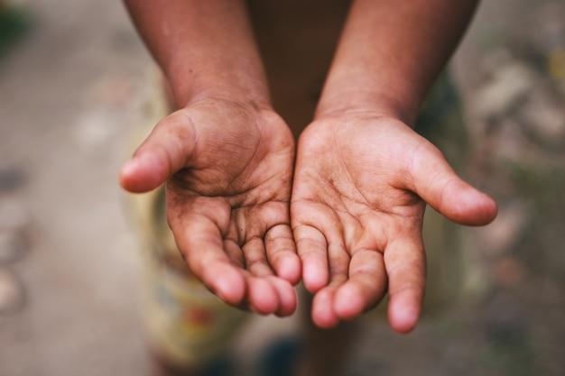 Mãos de uma criança sem-teto, implorando palma, implorando a mão, homem com fome.