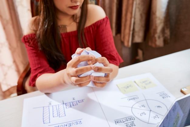 Mãos de uma empresária frustrada amassando papel após encontrar um grande erro no relatório