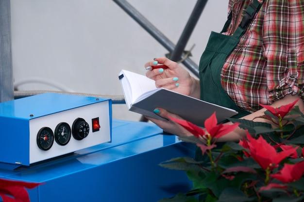 Mãos de uma engenheira agrícola anotando as leituras do sistema de aquecimento em uma estufa com flores vermelhas de amendoim