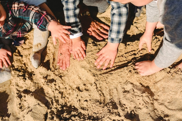 Mãos de uma família brincando com a areia na praia.