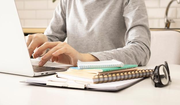 Mãos de uma freelancer feminina, trabalhando atrás da mesa em casa. ela está digitando algo no teclado de um laptop.