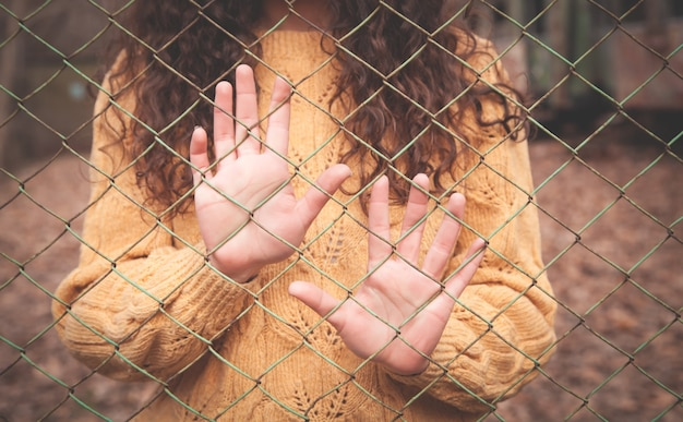 Mãos de uma garota caucasiana em uma cerca de arame.