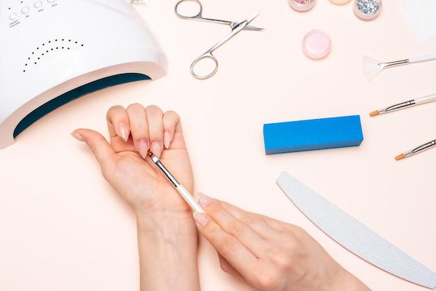 Mãos de uma garota fazendo as unhas, aplicando o gel com um pincel. a vista do topo