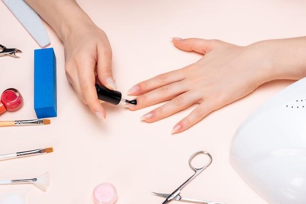 Mãos de uma garota fazendo as unhas em casa, close-up de mãos. a vista do topo