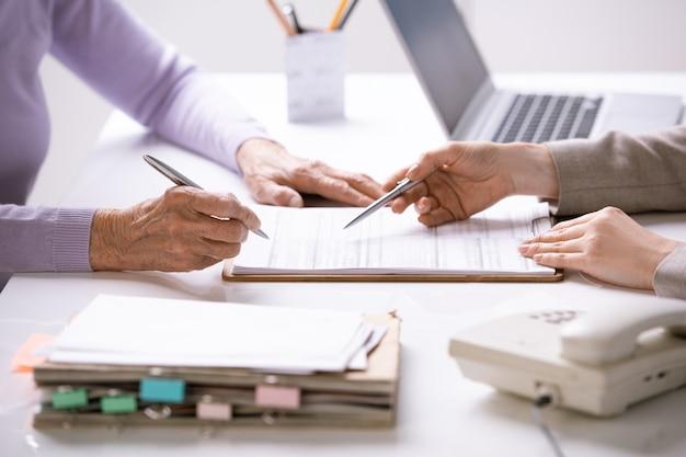 Mãos de uma jovem agente apontando para o documento de seguro e as de uma cliente sênior do sexo feminino para colocar sua assinatura nele