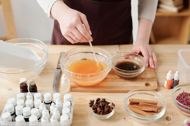 Mãos de uma jovem artesã misturando massa de sabão líquido com óleo essencial de laranja em uma tigela com uma vara de madeira