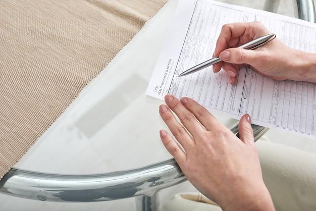Mãos de uma jovem assistente social com caneta sobre papel ajudando seu cliente a preencher o formulário de pedido de seguro saúde