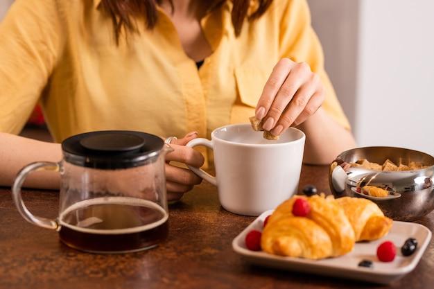 Mãos de uma jovem colocando dois cubos de açúcar mascavo em uma xícara com chá ou café enquanto vai tomar café da manhã