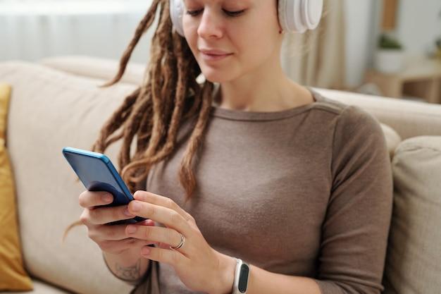 Mãos de uma jovem com fones de ouvido rolando no smartphone para ouvir músicas ou vídeos curiosos enquanto está sentado no sofá