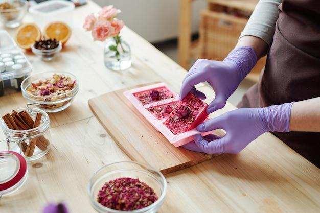 Mãos de uma jovem com luvas de borracha lilás tirando sabonete rosa artesanal fresco de moldes de silicone