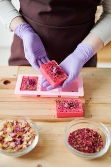 Mãos de uma jovem com luvas lilás segurando uma barra de sabonete rosa floral artesanal fresco sobre a mesa de madeira