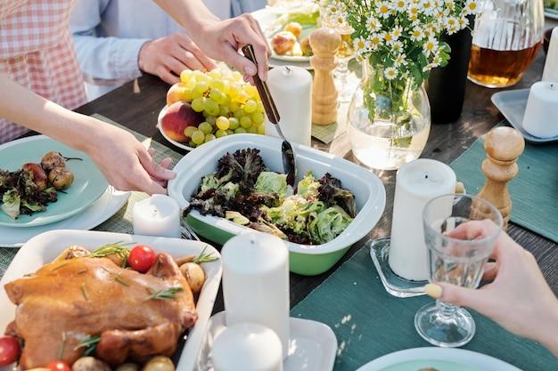 Mãos de uma jovem com uma colher pegando ou misturando legumes cozidos na mesa festiva servida com comida caseira entre amigos
