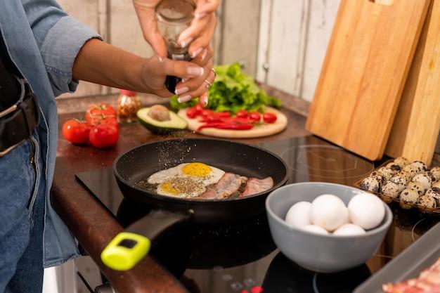 Mãos de uma jovem de jeans e camisa jeans, ao lado do fogão elétrico, polvilhando especiarias na frigideira com ovos fritos e bacon