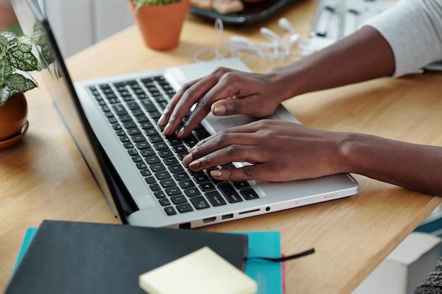 Mãos de uma jovem digitando no laptop ao trabalhar na mesa do escritório em casa