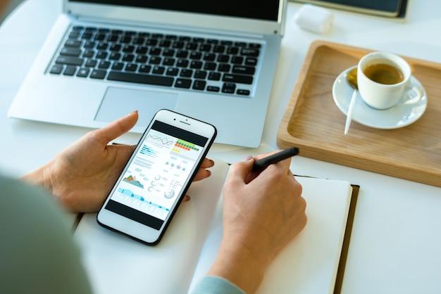 Mãos de uma jovem economista contemporânea analisando dados na tela do smartphone enquanto faz anotações no caderno