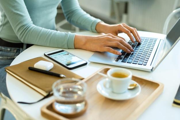 Mãos de uma jovem empresária ou freelancer em roupa casual tocando as teclas do teclado do laptop enquanto trabalha em rede à mesa no café