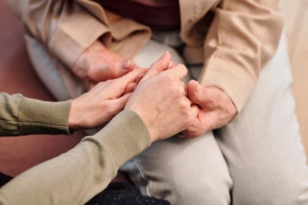 Mãos de uma jovem gentil segurando as de uma mulher madura em roupas casuais enquanto está sentado ao lado dela, apoiando e confortando-a em apuros