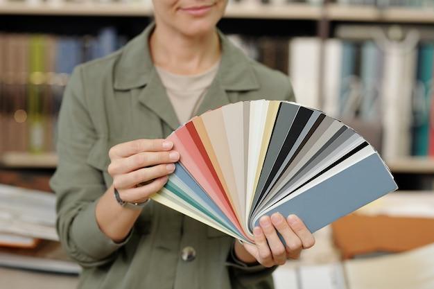Mãos de uma jovem gerente de estúdio de design de interiores mostrando paleta com amostras de couro novo para móveis contra o local de trabalho