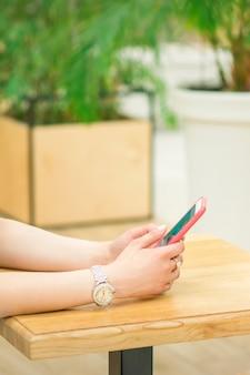 Mãos de uma jovem mulher branca segurando um smartphone sentado à mesa ao ar livre