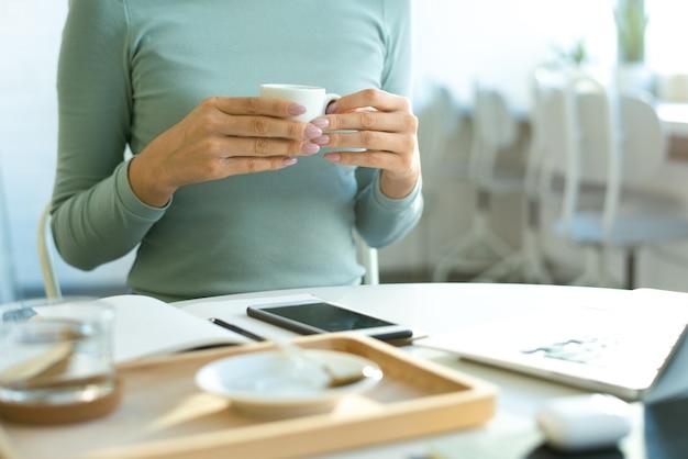 Mãos de uma jovem mulher casual segurando uma xícara de chá sobre a mesa com gadgets e abrir o caderno enquanto faz uma pausa no café