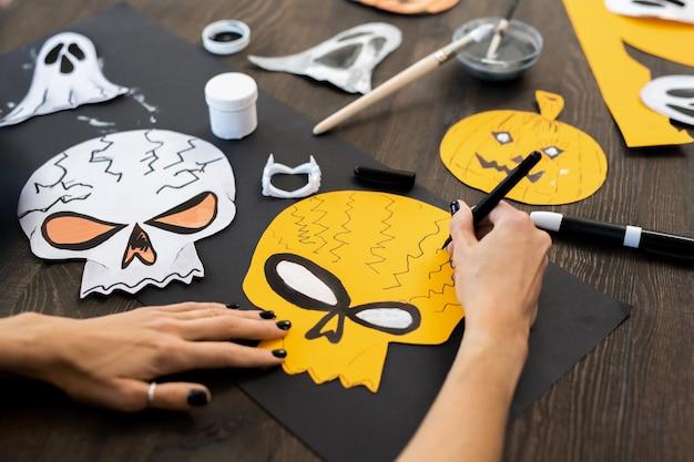 Mãos de uma jovem mulher desenhando crânios para o dia das bruxas