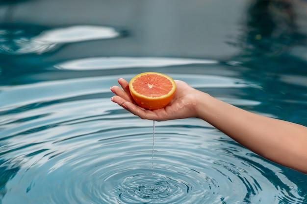 Mãos de uma jovem mulher segurando uma toranja vermelha próximo com água azul. comida saudável