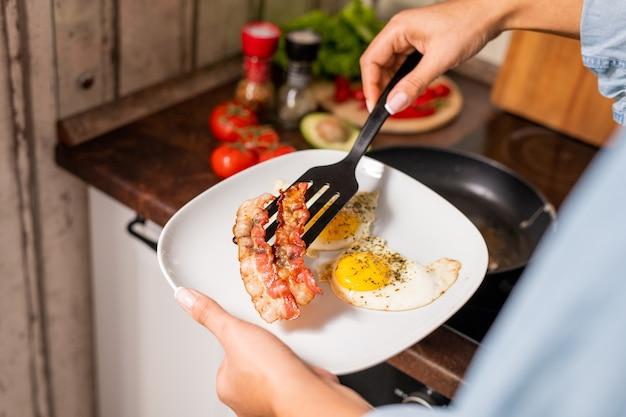 Mãos de uma jovem pondo ovos e bacon frito no prato enquanto esperava perto do fogão elétrico na cozinha e ia tomar café da manhã