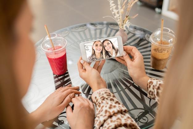 Mãos de uma jovem segurando um smartphone com uma selfie com a mãe, enquanto estão sentadas à mesa no café e tomando coquetéis