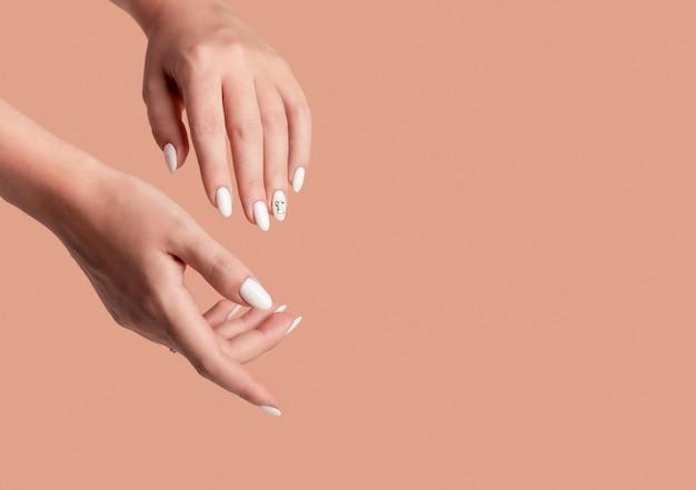 Mãos de uma linda mulher bem cuidada com unhas femininas em um fundo bege.