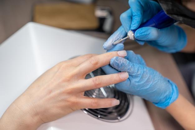 Mãos de uma manicure com removedor de esmalte e mão de mulher