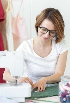 Mãos de uma marca de roupas de grife jovem para o novo produto com a ajuda de giz e fita métrica. conceito de design de roupas e produtos de autoria exclusivos