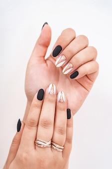 Mãos de uma menina com uma bela manicure combinada em exposição.