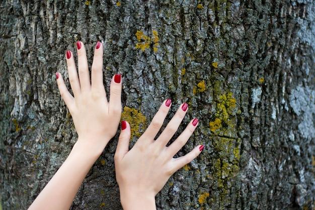 Mãos de uma menina com uma manicure na moda em um tronco de árvore. publicidade, demonstração de manicure. beleza e natureza