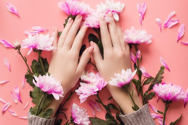Mãos de uma menina com uma manicure suave em flores