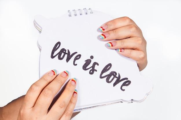 Mãos de uma menina com unhas pintadas nas cores do arco-íris segurando um caderno com amor é amor escrito
